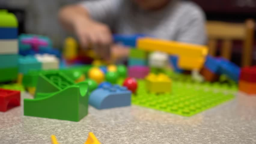 Little child playing with lots of colorful plastic toys indoor.    Shutterstock HD Video #1019639359