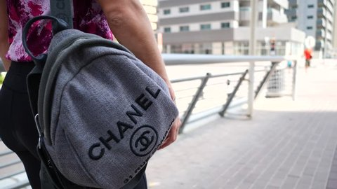DUBAI - OCTOBER, 2018: Woman with Chanel back pack bag walking on the street. Chanel is a high fashion house specialized in women's haute couture clothes, luxury goods, and fashion, and accessories.