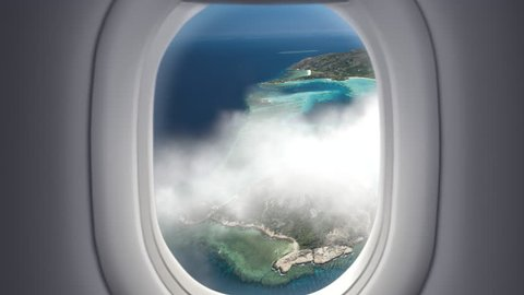 View from the window at passenger seat in airplane flight above clouds and sea with tropical islands