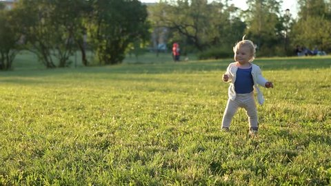 Caucasian cute girl child learns to walk on the green grass in the park at sunset and falls at the end