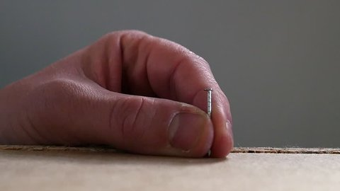 A nail is hammered in a flat pack in slow motion