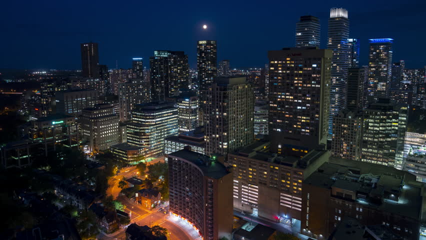The historic and modern Toronto architecture buildings with cars commuting and long exposure light streaks depict fast movement in a quick paced urban environment. The full moon rises over the city. | Shutterstock HD Video #1019847709