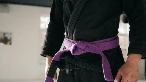 Karate purple belt tied around marital artists torso wearing black dojo GI's jiu jitsu mma fighter wearing gym ring