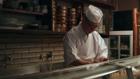 Experienced male sushi chef taking wasabi and rice and making a ball in hands in small traditional sushi bar with soft day lighting. Medium shot on 4k RED camera.
