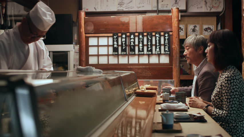 Content Japanese couple drinking tea and while waiting for lunch to be prepped by Master chef in small sushi bar with soft interior lighting. Close up shot on 4k RED camera. | Shutterstock HD Video #1019910559