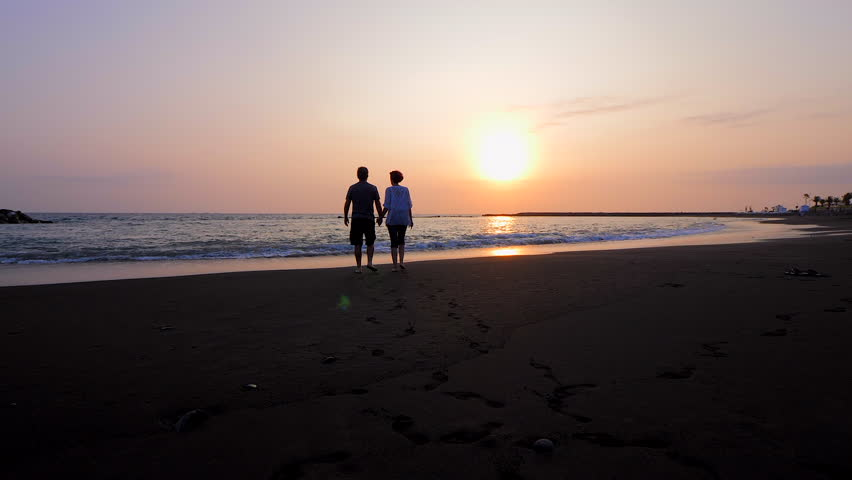 Man and woman holding hands and walking during the sunset with barefoot on a black sand beach in the south of the island of Tenerife. Slow-motion