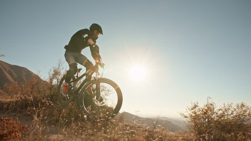 Mountain cycler riding up the path in mountains in sunset, following the trail or road, then doing cool jump - extreme, fitness, | Shutterstock HD Video #1019950579