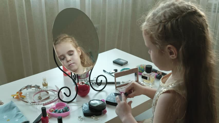 A little girl with red hair fastens hairpins on hair, tries on accessories, looks in the mirror, makeup, face, fashion, style, cosmetics portrait4k | Shutterstock HD Video #1019982019