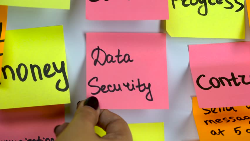 Hand glues a sticker with an inscription data security on a board | Shutterstock HD Video #1020041479