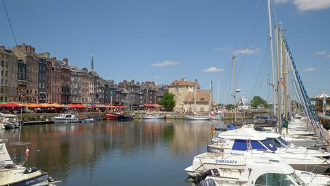 HONFLEUR, FRANCE - JUNE 2018: Honfleur harbour old port with beautiful houses and lots of yachts. Honfleur is located in the northern region of Calvados, Normandy, France.