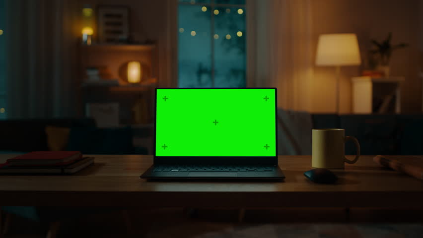 Laptop Computer Showing Green Chroma Key Screen Stands on a Desk in the Living Room. In the Background Cozy Living Room in the Evening with Warm Lights on. Zoom In Shot.