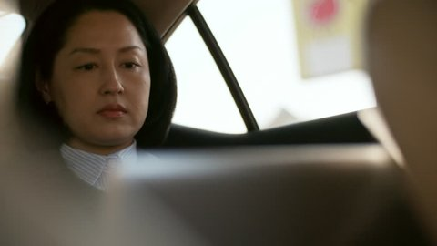 Medium shot of middle-aged Asian woman sitting in backseat of car and working on laptop computer