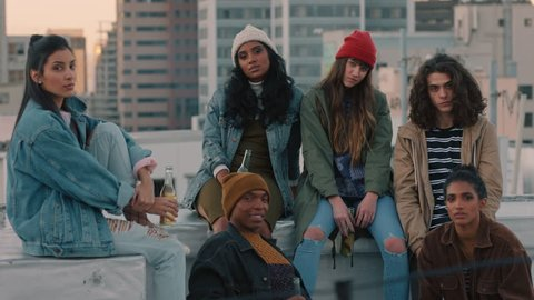 group of young diverse friends hanging out on rooftop at sunset looking confident in urban city gen z concept