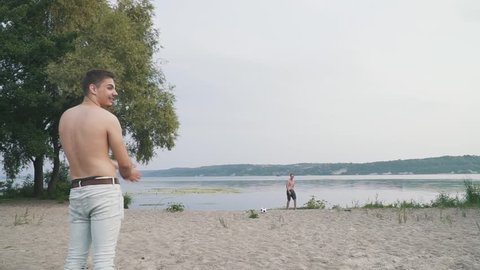 Two guys playing with a soccer ball on the beach near the river Two friends playing with the ball outdoors Friends have a fun together Spending time outdoors Active lifestyle