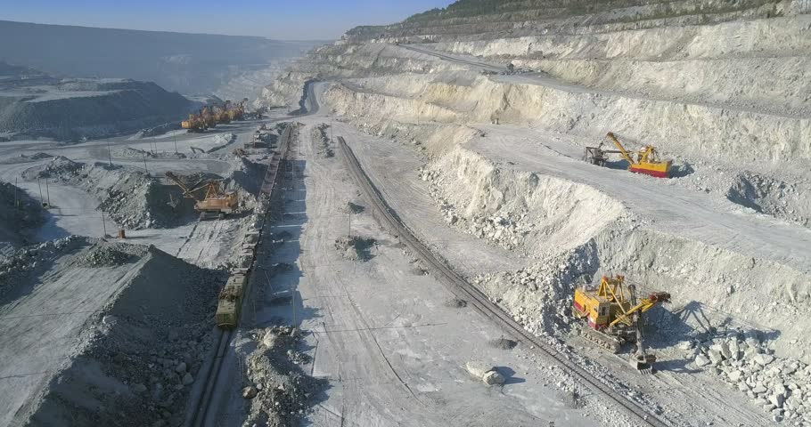 Aerial motion over mining site with digging excavators and loaded train on railway in asbestos pit | Shutterstock HD Video #1020253399