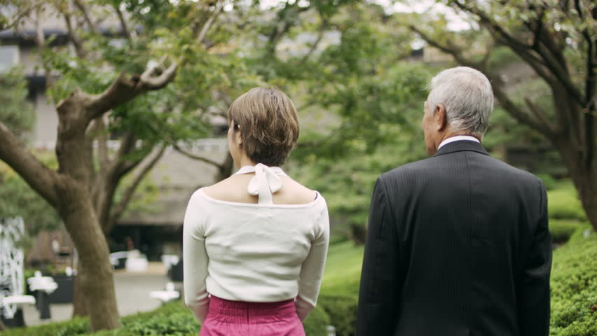 Young adult woman walking and talking with an elderly man along a path in a vibrant garden with soft natural lighting. Medium shot on 4k RED camera.