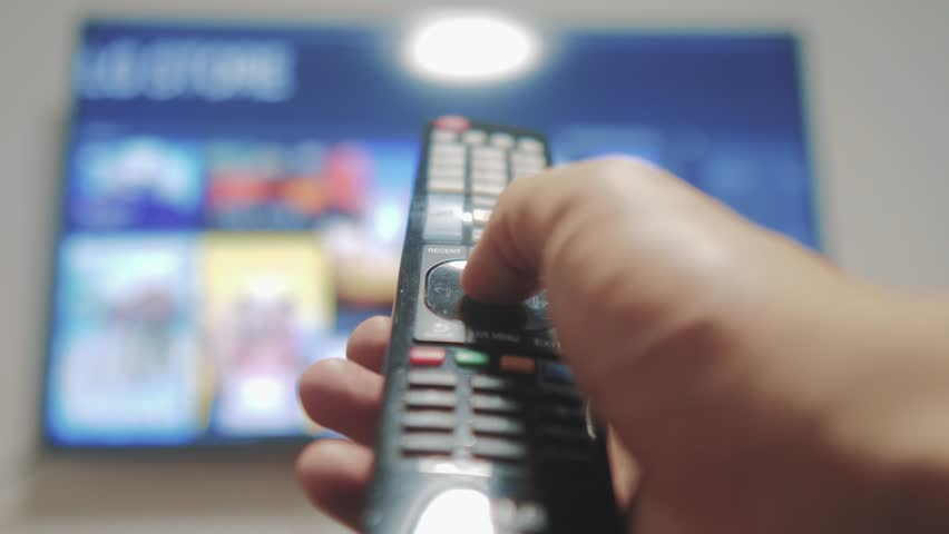Smart tv with apps and hand. Male hand holding the remote control turn off smart tv . man hand controls TV holding remote. TV concept lifestyle internet online cinema | Shutterstock HD Video #1020338509