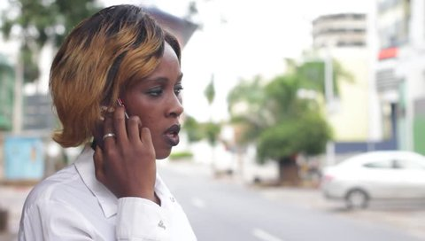 young girl standing in white shirt sneezing while talking on mobile phone.