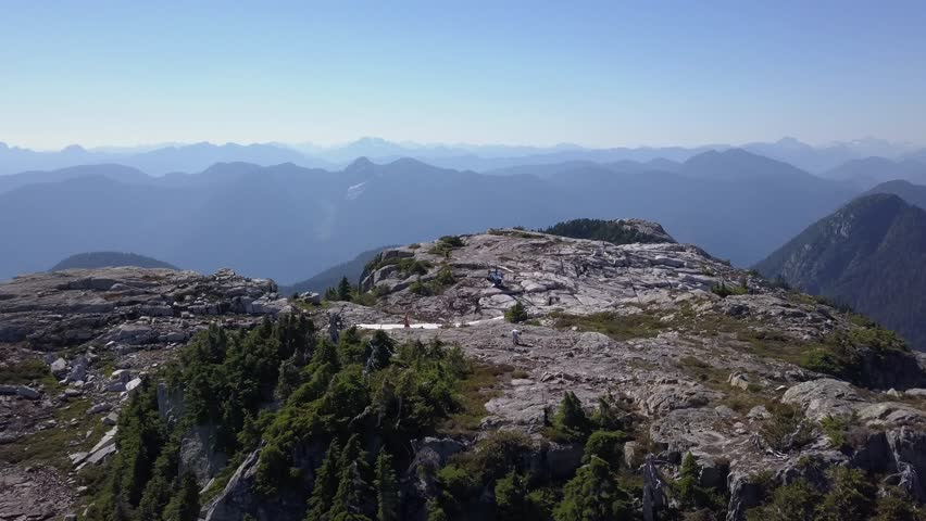 Helicopter on BC mountain top peak aerial drone shot in 4k. Summer time with some snow open landscape view of distant Rocky Mountains. Canada, British Columbia close to Vancouver, Whistler #1020388159
