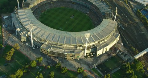 Melbourne - March 2018: Aerial view at sunset Melbourne Cricket Ground sports stadium with floodlights alongside railway tracks Yarra Park Victoria Australia
