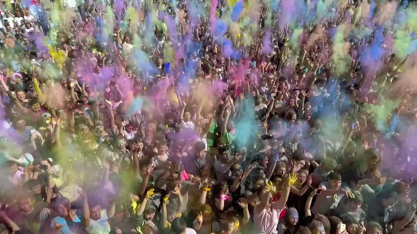 Kharkiv, Ukraine - Apr 30, 2017: aerial of Holi colours festival in slow motion. people throwing colourful powder in the air #1020399799