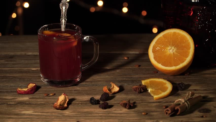 Hand is stirring mulled wine standing on the table with orange and dried apples | Shutterstock HD Video #1020403249