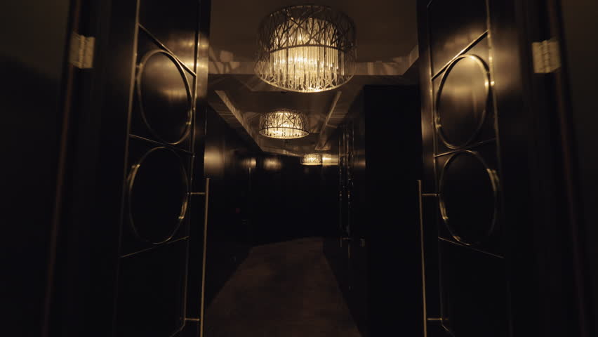 A steadicam shot through a hotel lobby with two elevators to a dark luxurious hallway. Beautiful chandeliers have warm muted light. Dark shiny doors are styled with geometrical metal details | Shutterstock HD Video #1020408109