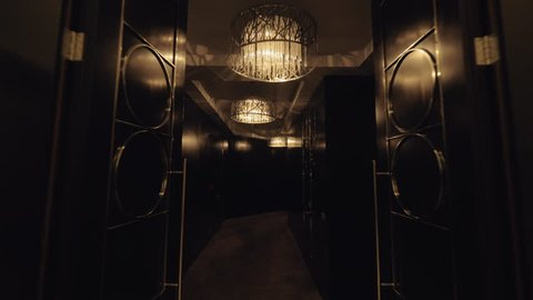 A steadicam shot through a hotel lobby with two elevators to a dark luxurious hallway. Beautiful chandeliers have warm muted light. Dark shiny doors are styled with geometrical metal details