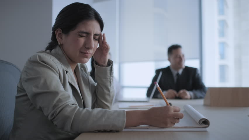 Tired business woman working in office meeting room during conference. Busy latina girl with headache at work. Ill latina businesswoman with flu in corporate room. Health problem, anxiety and pain | Shutterstock HD Video #1020411259