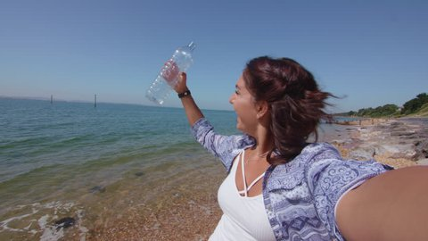 POV Shot Of Young Woman Reaching Down To Pick Up Plastic Bottle On Beach In Slowmotion