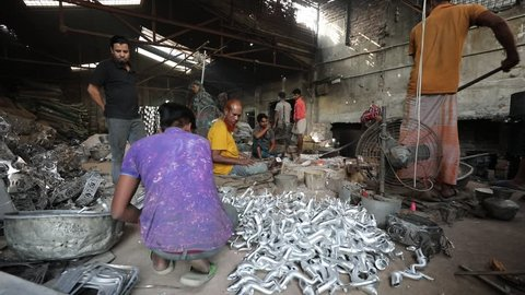 DHAKA, BANGLADESH - DECEMBER 01, 2018: Aluminium factory sweatshop with children and adults working in dangerous and unsafe circumstances making aluminium teapots