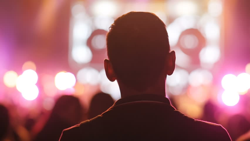 Close-up back of young man looking forward. Silhouette of concert crowd, backstage. Night, flashes, lights. | Shutterstock HD Video #1020531259