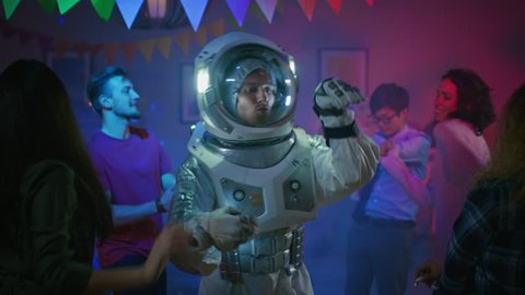 At the College House Costume Party: Fun Guy Wearing Space Suit Dances Off, Doing Groovy Funky Robot Dance Modern Moves. With Him Beautiful Girls and Boys Dancing in Neon Lights. In Slow Motion.