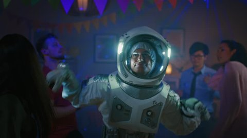 At the College House Costume Party: Fun Guy Wearing Space Suit Dances Off, Doing Groovy Funky Robot Dance Modern Moves. With Him Beautiful Girls and Boys Dancing in Neon Lights.