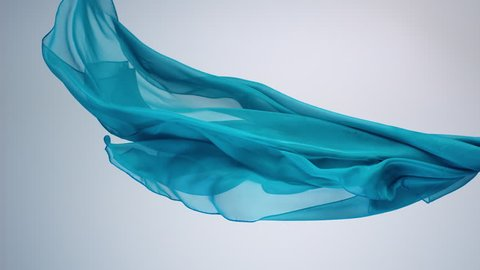 Green transparent fabric flowing by wind, slow motion