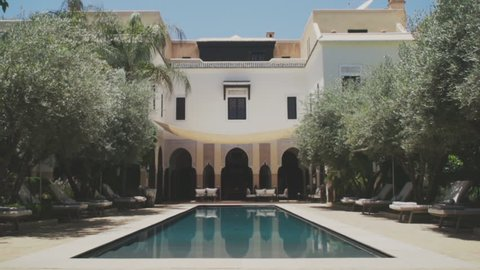Marrakech, Morocco July 2018. Luxury Hotel Villa des Orangers on a hot sunny day in the center of Marrakech near to  The Koutoubia Mosque in super slow motion. Beautiful swimming pool to relax.