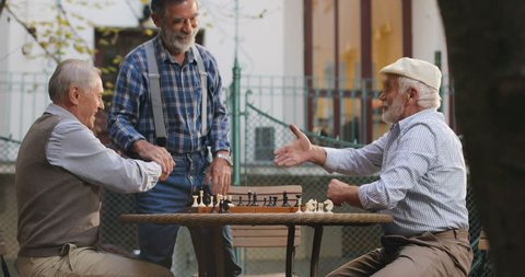 Caucasian senior men neighbors having a chess game in the yard and their old friend coming to join them, greeting, shaking hands and sitting next to them. Outdoors.