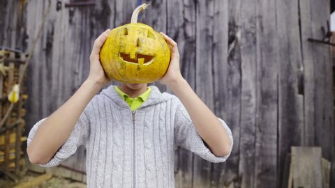 Boy holding a pumpkin head in front of own head HD. Sliding in front of boy portrait shot holding proud his cut out face in big pumpkin. Dressed in woolen sweater.