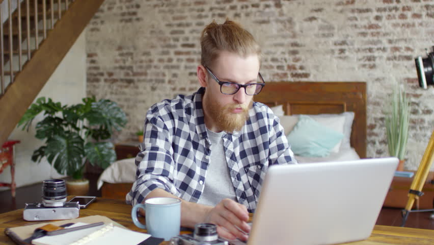 Tilt down shot of young bearded man in glasses sitting at his desk and working on laptop in loft apartment. Planner, film cameras and mug on table | Shutterstock HD Video #1020628969