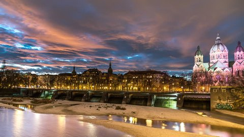 Munich skyline at night view of river isar and church St. Luke's Church Bavaria Germany time lape with dramatic louds.