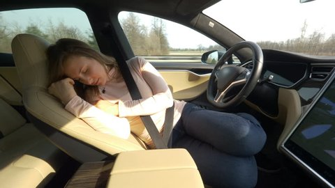 CLOSE UP: Exhausted female driver sleeps tightly in her car set on auto pilot. Young Caucasian woman enjoying a tranquil road trip by napping in a self driving vehicle. Tired tourist girl sleeping.