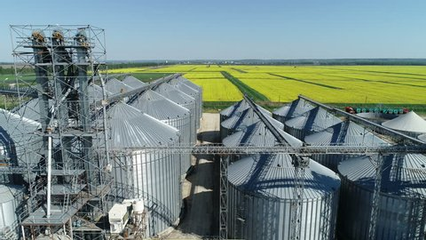 Aerial view of agricultural land and grain silo. Steel Grain Silos Elevators Storage 4K Aerial Video. Agriculture Industry