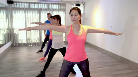 young sporty people opening hands arms in line face to mirror in yoga practice exercise class in gym. carefree athletic asians wearing tank top strength body indoor in classroom in fitness club.