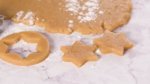 Raw dough for christmas cookies and cookie cutters on marble surface.