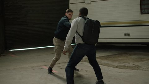 Weaker man is punched by a strong man in front of an abandoned camper trailer in an old warehouse in moody lighting. Medium shot in 4K with an Alexa Mini camera
