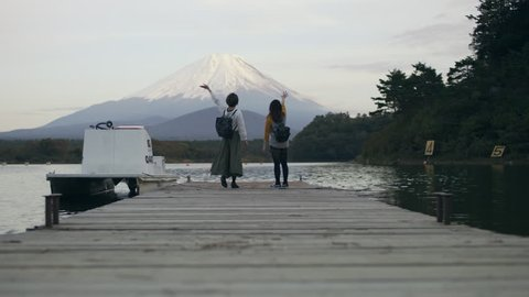 Wide shot on 4k RED camera. Excited Japanese women running up a dock on the water to see Mount Fuji and happily waving at it with soft natural lighting.