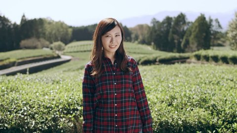 Portrait of a happy Japanese woman standing in front of a tea plantation with bright natural lighting. Medium shot on 4k RED camera.