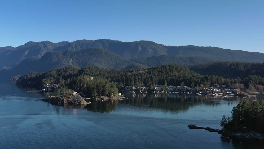 Aerial view over Burrard Inlet, ocean and island with boat and mountains in beautiful British Columbia. Canada. | Shutterstock HD Video #1020790429