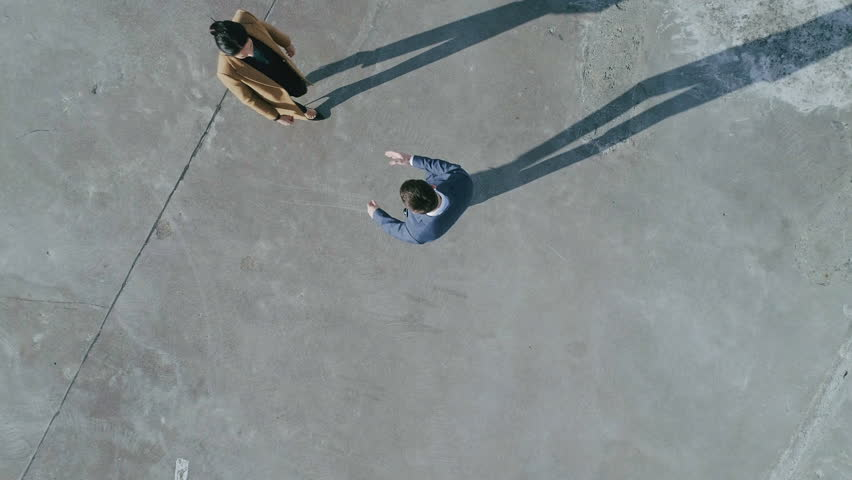 Top Down Aerial Drone Footage: Two Businesspeople Meeting on Industrial Concrete Setting. Businesspeople do Handshake, Ready for Business Deal.