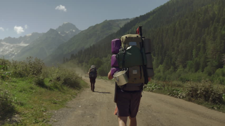 Two travellers walking on the mountain road | Shutterstock HD Video #1020811009